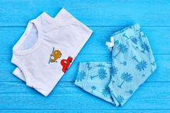 Set of patterned kids summer wear. New childs printed clothing on blue wooden background. Children summer garment Stock Photos