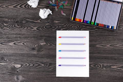 Set of pencils on old boards. Crayons on a sheet of paper. Idea Royalty Free Stock Photo
