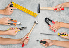 Set of peoples hands holding tools. Set of peoples hands holding different tools on grey background Royalty Free Stock Images
