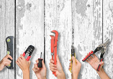 Set of peoples hands holding tools. Set of peoples hands holding different tools on white board texture background royalty free stock image