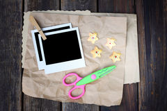 Set of photo frame scissors and crumpled paper on wooden background Stock Photos