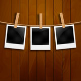 Set of photo frames on the rope with clothespin. Polaroid photo frames set on wooden background.  Royalty Free Stock Images