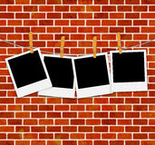 Set of photo frames on rope with clothespins on brick wall Royalty Free Stock Photos