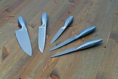 Set pięć stalowych kuchennych knifes na drewnianym stole Obrazy Stock