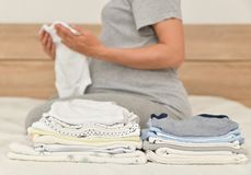 Pile of baby clothes and pregnant woman on a bed. Set or pile of baby clothes and pregnant woman on a background royalty free stock photo