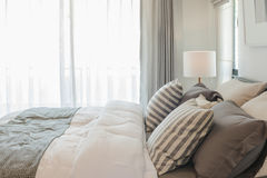 Set of pillows and blanket on bed in modern bedroom Royalty Free Stock Image