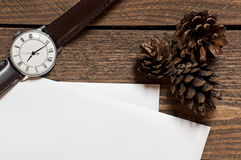 Set of pines watch and paper sheets on wooden table Stock Image