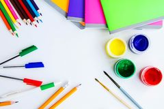 Set of plastic cans with colored paints, brushes, pencils, pens and colored notebooks on white background. Drawing tool. Top view royalty free stock photography
