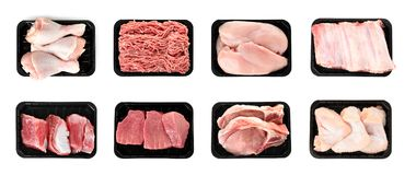 Set of plastic containers with different raw meat on white. Background, top view royalty free stock photography