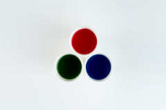 Set of plastic cups with red, green and blue paints isolated on grey Royalty Free Stock Image