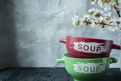 A set of plates for soup with the inscription. The branch is blossoming apricots. Place for text. Dark wooden background stock photography