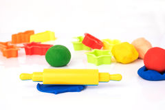 Set of play dough and plastic cutting block on white. Royalty Free Stock Images