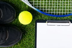 Set for playing tennis lies on a green lawn as a background Stock Photos