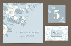 Set polygraphy to celebrate the wedding. Invitation card, table number, guest card. Romantic set with a branch of blossoming dog-rose on blue-gray background Royalty Free Stock Photos