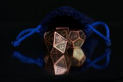 A set of polyhedral dice used for role playing games such as Dun. A set of polyhedral dice  with a blue drawstring bag on a mirrored surface. These dice are used Royalty Free Stock Photos
