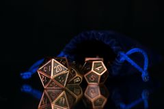 A set of polyhedral dice used for role playing games such as Dun. A set of polyhedral dice  with a blue drawstring bag on a mirrored surface. These dice are used Royalty Free Stock Photography