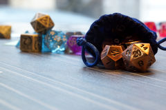 A set of polyhedral dice with a draw string bag. A set of polyhedral dice used for role playing games such as Dungeons & Dragons, the dice are used to determine Royalty Free Stock Image