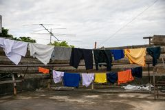A set of primary colored T-shirts hanging on a clothesline on a white sky stock photography