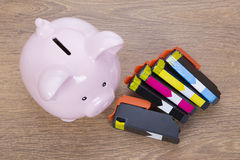 Set of printer ink cartridges with a piggy bank stock photo