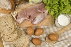 Set products consisting of bread, milk, pork, eggs , and vegetable on wooden table background stock photo