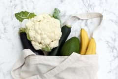 Set of products in a cotton bag on a marble table, bananas, avocado, eggplant, zucchini, cauliflower. The concept of zero waste. Set of products in a cotton eco royalty free stock photography