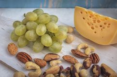 A set of products: grapes, different nuts on a wooden background, wooden old kitchen board stock image