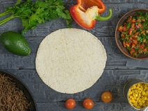 A set of products with tortillas for Mexican tacos. The view from the top. Cake made of corn flour, avocado, pepper, lemon, lime, parsley, corn. Ingredients for Royalty Free Stock Image