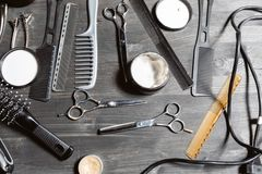 Set of professional hairdresser tools on grey background. Wooden table in barbershop. Working tool of barber master.  stock images
