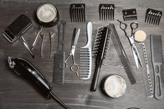 Set of professional hairdresser tools on grey background. Wooden table in barbershop. Working tool of barber master.  royalty free stock photo