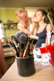 Set of professional makeup brushes against artist doing makeup Stock Image