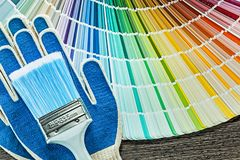Set of protective gloves paintbrush color palette on wooden boar. D stock photography