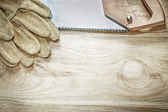 Set of protective gloves stainless handsaw on wooden board const Stock Photography