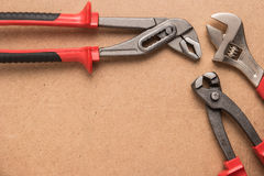 Set of pump plier, plier and wrenches. Tools over a wood panel. Stock Image