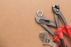 Set of pump plier, plier and wrenches. Tools over a wood panel. Stock Photo
