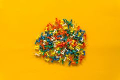Set of push pins in different colors. Thumbtacks. Top view. on Yellow background. Space royalty free stock photos