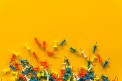 Set of push pins in different colors. Thumbtacks. Top view. on Yellow background. Space stock image