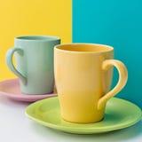 Set puste kolorowe ceramiczne filiżanki dla kawy odizolowywającej na barwionym tle obraz royalty free