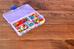 Set różni drewniani koraliki w organizatorze na brown drewnianym tle z kopii przestrzenią dla teksta Obrazy Stock