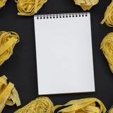 Set różnorodny uncooked pastafettuccine, pappardelle, tagliolini i pustego miejsca notatnik na czerni powierzchni, odgórny widok  zdjęcie royalty free