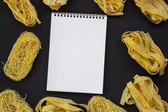 Set różnorodny uncooked pastafettuccine, pappardelle, tagliolini i pustego miejsca notepad na czarnym tle, zasięrzutny widok zdjęcie royalty free