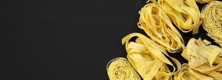 Set różnorodny uncooked pastafettuccine, pappardelle, tagliolini na czerni powierzchni, odgórny widok Mieszkanie nieatutowy, od a fotografia stock
