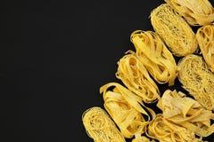 Set różnorodny uncooked pastafettuccine, pappardelle, tagliolini na czerni powierzchni, zasięrzutny widok Mieszkanie nieatutowy,  obrazy royalty free