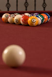 Billiard (pool) Balls. A set of racked billiard balls on a red felt table top with a cue ball out of focus in the foreground Royalty Free Stock Image