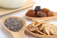 Set of raisins, whole wheat grain flakes and chia seeds in woode Stock Photos