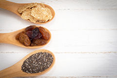 Set of raisins, whole wheat grain flakes and chia seeds in woode Royalty Free Stock Photography