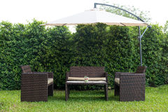 Set of rattan garden furniture under a big garden umbrella Stock Photos