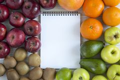 Set of raw fruits with notebook. On white wooden background. Healthy food concept, top view. Flat lay. Summer background Royalty Free Stock Photography