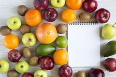 Set of raw fruits with notebook. On white wooden background. Healthy food concept, top view. Flat lay. Summer background Stock Images