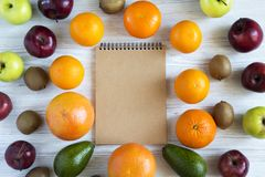 Set of raw fruits with notebook on white wooden background. Healthy food concept, top view. Flat lay. Summer background Stock Photo