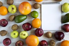 Set of raw fruits with notebook on white wooden background. Healthy food concept, top view. Flat lay. Summer background Stock Photography